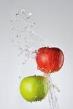 Manzanas y chapoteo rojos, verdes del agua Fotos de archivo libres de regalías