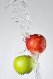 Manzanas y chapoteo rojos, verdes del agua Imagen de archivo libre de regalías