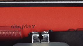 Chapter 1 - Typed on a old vintage typewriter. Printed on red paper. The red paper is inserted into the typewriter.  stock footage