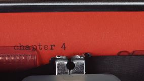 Chapter 4 - Typed on a old vintage typewriter. Printed on red paper. The red paper is inserted into the typewriter stock video