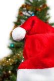 Chapéu de Santa no fundo das árvores Fotos de Stock Royalty Free