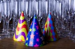 Chapéus do partido e flautas de vidro Fotos de Stock Royalty Free