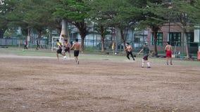 Chaque soirée en parc public ont des personnes de diversité jouant au football ensemble au terrain de football pour fort Près du  banque de vidéos