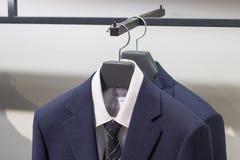 Chaqueta azul en una suspensión, vista delantera del primer, en la tienda de la ropa de los hombres imágenes de archivo libres de regalías