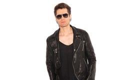 Chaqueta de cuero que lleva y gafas de sol del hombre fresco del rock-and-roll imagen de archivo
