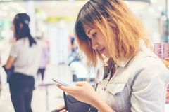 Chaqueta de la mezclilla de la mujer que lleva hermosa joven que manda un SMS en el smartph Imagen de archivo