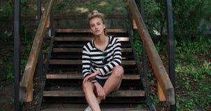 Chaqueta del dril de algodón de la muchacha que lleva elegante feliz que se sienta en las escaleras de madera en un parque de la  Fotos de archivo libres de regalías
