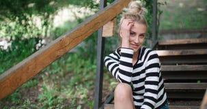 Chaqueta del dril de algodón de la muchacha que lleva elegante feliz que se sienta en las escaleras de madera en un parque de la  Imagenes de archivo