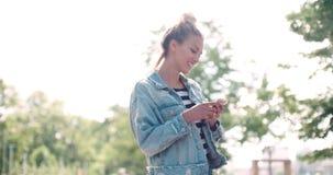 Chaqueta hermosa del dril de algodón de la mujer que lleva joven que mecanografía en el teléfono en un parque de la ciudad Fotografía de archivo