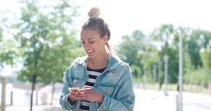 Chaqueta hermosa del dril de algodón de la mujer que lleva joven que mecanografía en el teléfono en un parque de la ciudad Imágenes de archivo libres de regalías