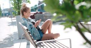 Chaqueta hermosa del dril de algodón de la mujer que lleva joven que mecanografía en el teléfono en un parque de la ciudad durant Foto de archivo