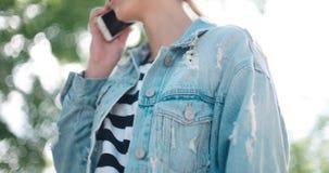 Chaqueta irreconocible del dril de algodón de la mujer que lleva joven que habla en el teléfono durante día soleado Imagen de archivo