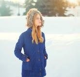 Chaqueta que lleva de la mujer de la moda del invierno con la capilla en la cabeza sobre nieve Imagen de archivo