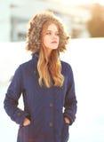 Chaqueta que lleva de la mujer del retrato de la moda del invierno con la capilla en la cabeza sobre nieve Imagen de archivo