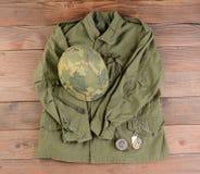 Chaqueta y casco de campo del ejército en el piso de madera Fotografía de archivo libre de regalías