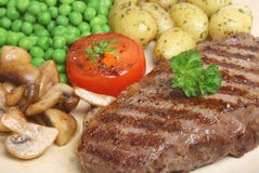 Char-grilled Steak Dinner. Char-grilled sirloin steak with sauteed musrooms, peas and new potatoes royalty free stock photo