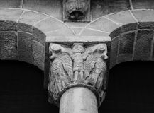 Character on the capital. Shot in black and white, detail on the sculpture on the  facade of this historic church representing a male character with some animals Stock Photo