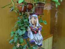 Cute handmade doll sits among the foliage of a houseplant royalty free stock images