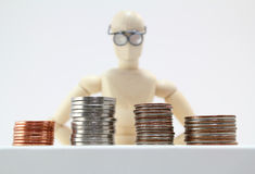 Character with glasses looking at coins. Royalty Free Stock Photo