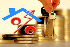 The character of the property and the keys on the background of bars coins . The concept of financial instability on the real estate market Stock Image