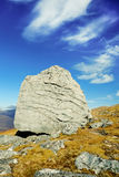Characterful Rock on a Scottish Mountain Pass. A huge glacial boulder stone sits immoveable on a high mountain pass in the Scottish Highlands, framed by an azure stock photos