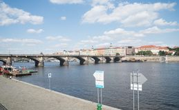 Characteristic architecture across river. PRAGUE, CZECH REPUBLIC - AUGUST 29, 2017; Characteristic architecture and tourist boats alongside promenade across Royalty Free Stock Photography