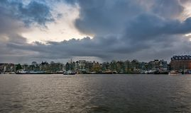 The characteristic canal houses and moored ships along the Ooste. Amsterdam, Netherlands, December 16, 2017: The characteristic canal houses and moored ships Royalty Free Stock Image