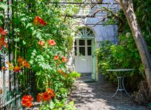 Characteristic entrance of a country house. Cozy entrance of a country house with flowers and garden table Stock Photos