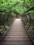 Characteristic pedestrian wooden bridge with a metal grating par. Apet that resembles the shape of a tunnel Royalty Free Stock Image