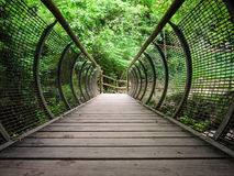 Characteristic pedestrian wooden bridge with a metal grating par. Apet that resembles the shape of a tunnel Royalty Free Stock Photos