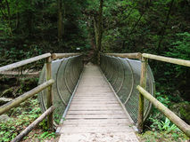 Characteristic pedestrian wooden bridge with a metal grating par. Apet that resembles the shape of a tunnel Stock Photography