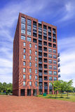 Characteristic red brick apartment building against a blue sky with dramatic clouds, Tilburg. Netherlands Royalty Free Stock Photography