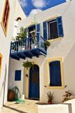 The fragment of characteristic white street of Greece with the blue balcony, windows and vases with flowers. Mandraki. Greece. royalty free stock image