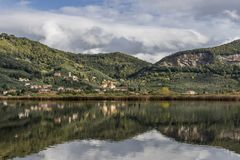 The characteristic village of Massaciuccoli is reflected in the waters of the homonymous lake, Lucca, Tuscany, Italy. Europe stock image