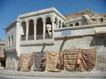 Characteristic white ancient building with pending carpets on the wall in the village of Mustafapasa in Cappadocia Turkey. royalty free stock photo
