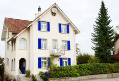 Characteristic white house with blue windows in Bremgarten, Switzerland Royalty Free Stock Photography