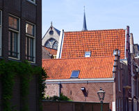 Characteristically Dutch street view. Orange tiled, stairstep gabled roofs and a church and its spire make for an unmistakebly Dutch street view in the very old stock photography