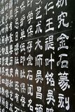 Characters Carved. White Chinese Characters Carved on Black Stone Wall Stock Photography