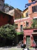 Charakteristischer Hof des alten Roms mit den roten Gebäuden und der verschobenen Wäscherei Italien Stockfotos