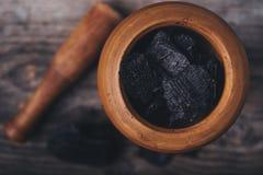 Charbon de bois dans un mortier en bois à bord Images libres de droits