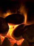Charbons chauds brûlant avec la flamme orange Photographie stock libre de droits