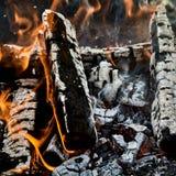 Charbons chauds et rondins carbonisés de bois dans un feu photographie stock