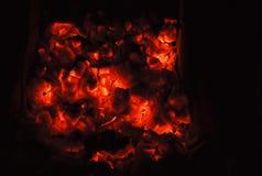 Charbons d'un rouge ardent sur le noir Photo libre de droits