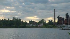 Charca de la ciudad cerca de la orilla un camino con la circulación densa después de la puesta del sol, lapso de tiempo metrajes