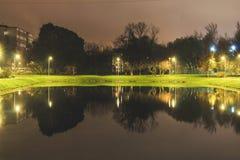 Charca de la ciudad con la iluminación alrededor del radio con la reflexión de luces imagen de archivo