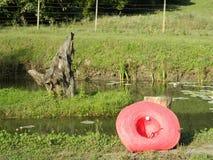 Charca de pesca con el sombrero rojo en frente Foto de archivo