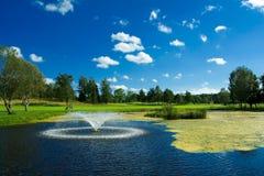 Charca del golf con el fontain Fotos de archivo