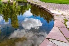 Charca hermosa del jardín con las trayectorias de piedra de la pavimentadora durante verano Fotos de archivo