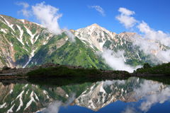 Reflexión de la montaña en la charca Foto de archivo libre de regalías