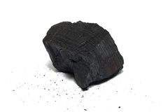 Charcoal. Bit of charcoal isolated on white with crumbs around Royalty Free Stock Photography